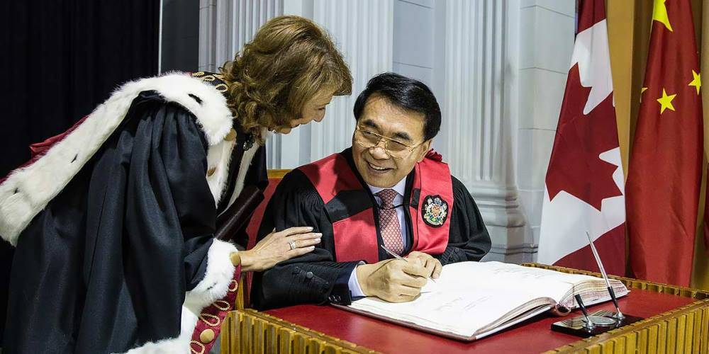Chinese Academy of Sciences president Chunli Bai signs the official registry after receiving an honorary doctorate from the University of Ottawa as Mona Nemer, Vice-President, Research, looks on