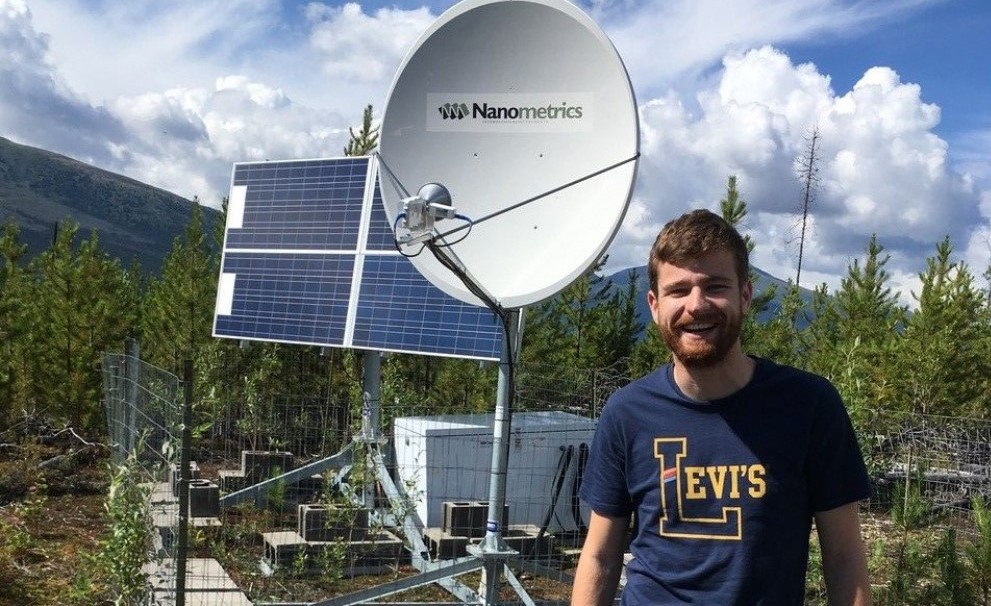 A smiling graduate student stands in front of a seismic station in a sparse forest of evergreens. There is a satellite dish and a solar panel behind them.