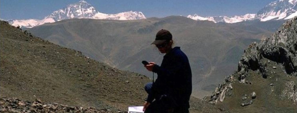 A student takes readings off a device surrounded by mountains