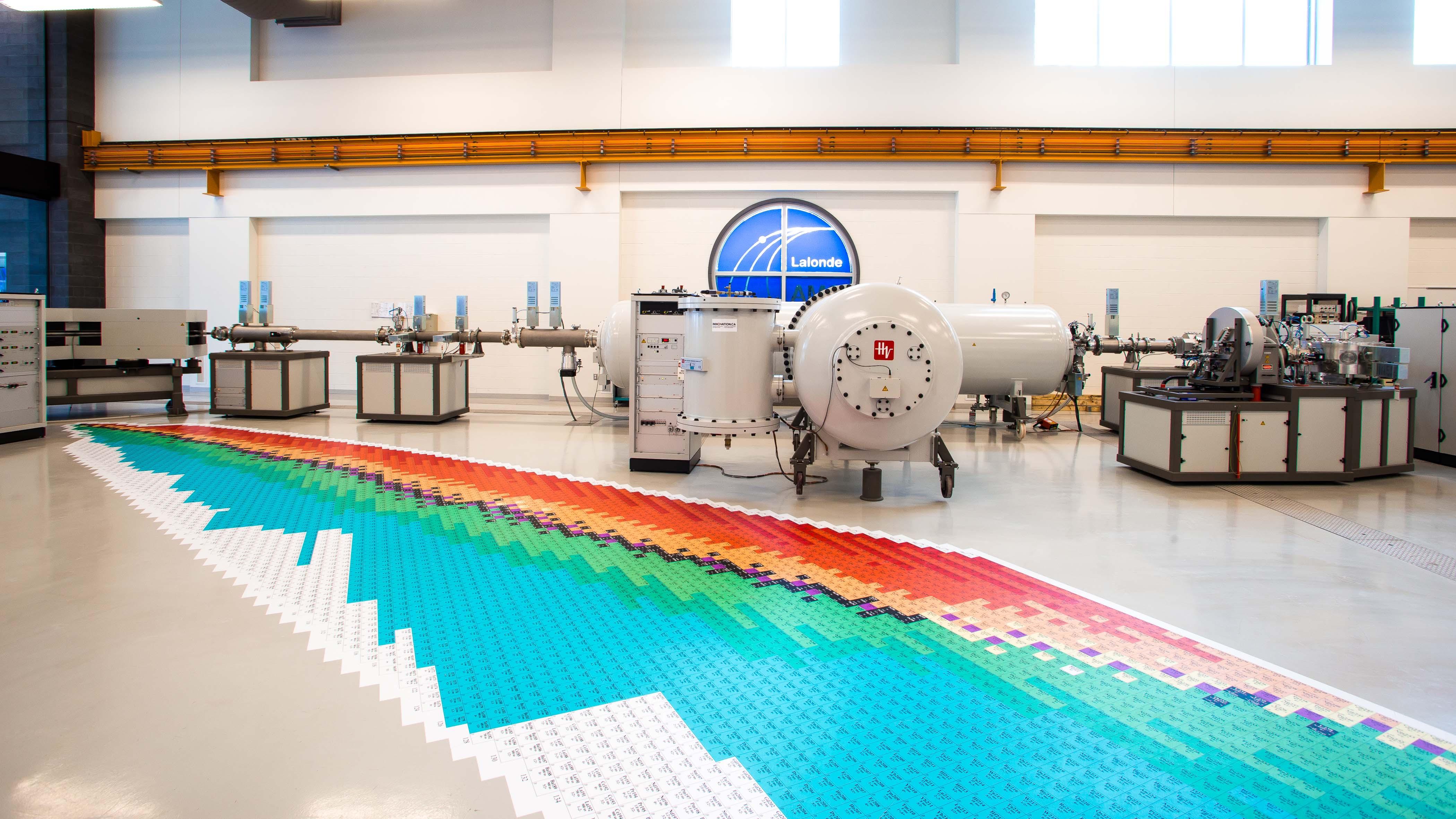 Intérieur du laboratoire avec un immense tableau périodique imprimé sur le sol