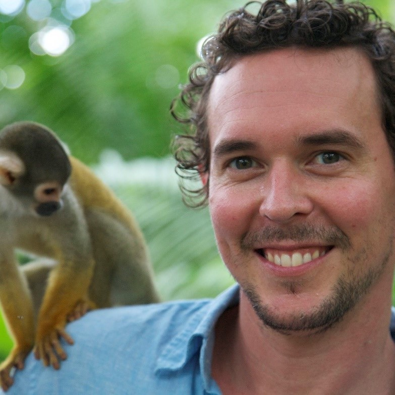 Prof. Adam Brown posing with a small monkey on his shoulder