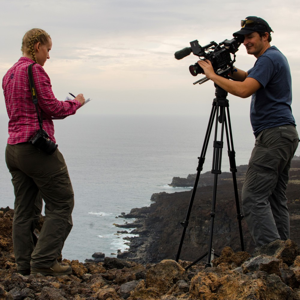 Two people, a man and a woman, are standing on a cliff by the sea. The man holds a camera on a tripod and films the woman writing in a notebook
