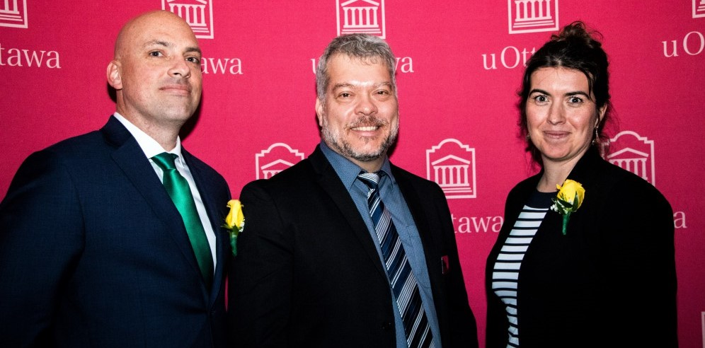 Alumni Valerie Langlois and David Morris Johnston-Monje posing in front of the uOttawa backdrop with Dean Louis Barriault