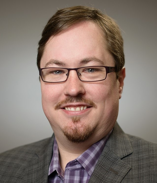 Headshot of former postdoctoral fellow Andrew Schaeffer, wearing a grey blazer over a purple shirt and in front of a light grey background.