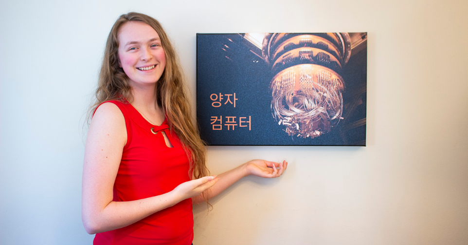 "Angéline Lafleur stands next to a mounted photograph of a quantum computer. The Korean characters read ""quantum computer."""