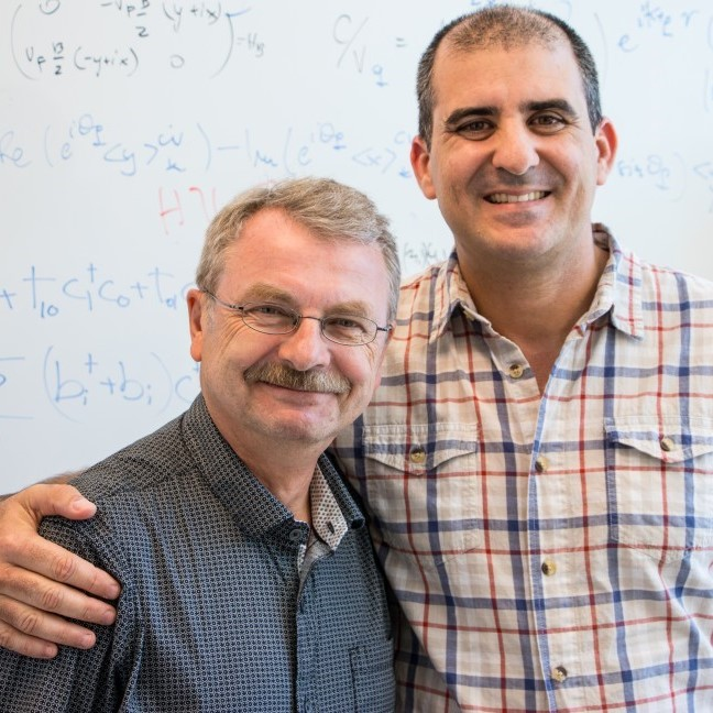 From Left to right, Professor Pawel Hawrylak and Adjunct Professor Marek Korkusinski are standing together in front of a white board, upon which various formulas are written in blue and red ink.