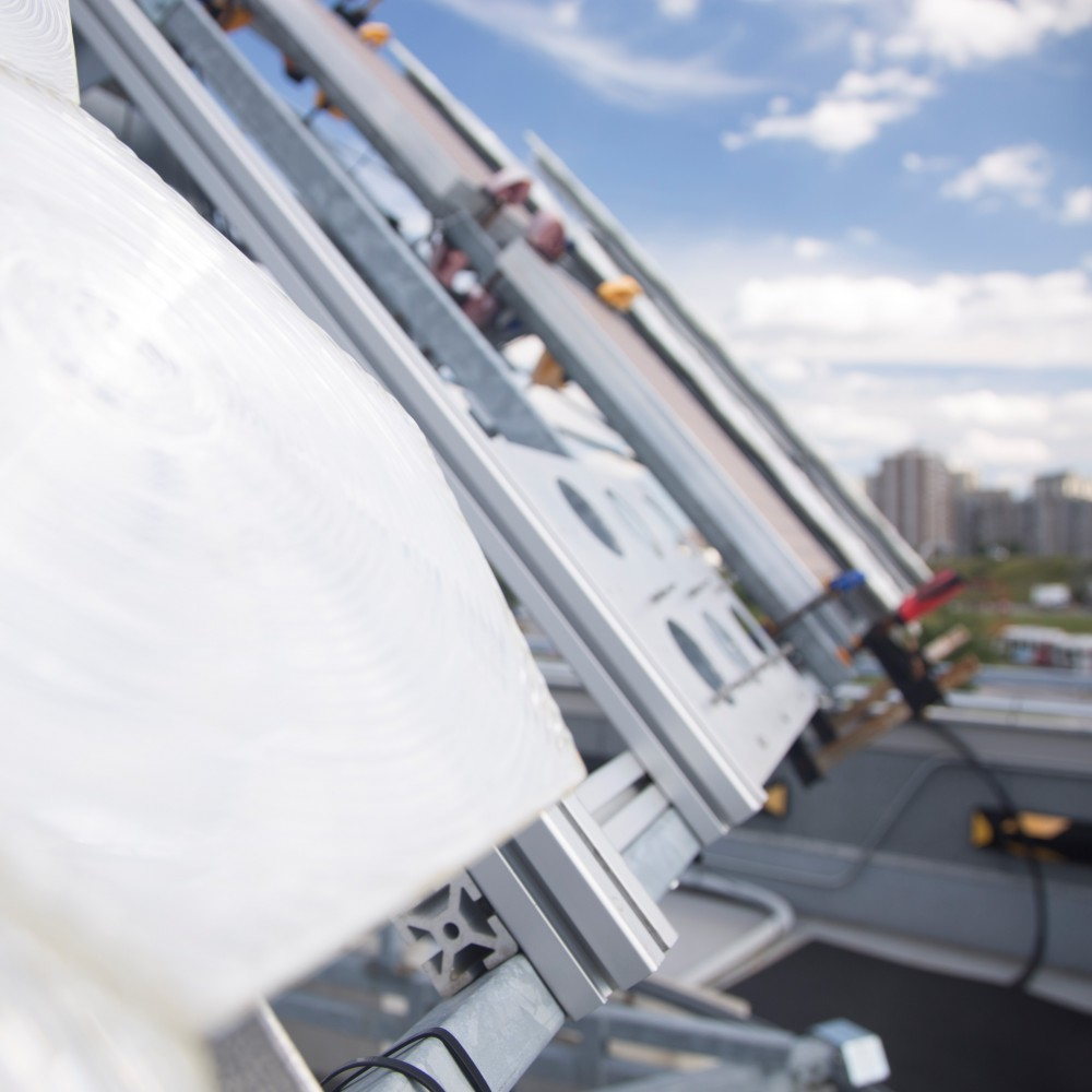 Metal panels and supports as well as a white canvas are fixed on the roof of a building.