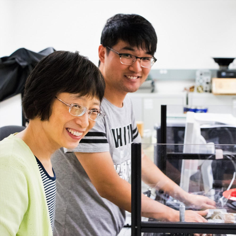 From left to right, Professor Xiaoyi Bao is standing beside PhD student Song Gao, whose hands are inside a three-walled see-through plastic box. They are both smiling and looking towards the camera