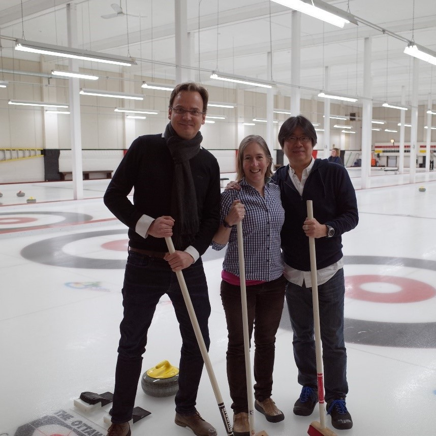 (from left to right) Professors Auke Ijspeert (EPFL, Switzerland), Emily Standen (University of Ottawa) and Aiko Ishiguro (Tohoku University, Japan) stand side-by-side on a curling rink, each holding curling brooms