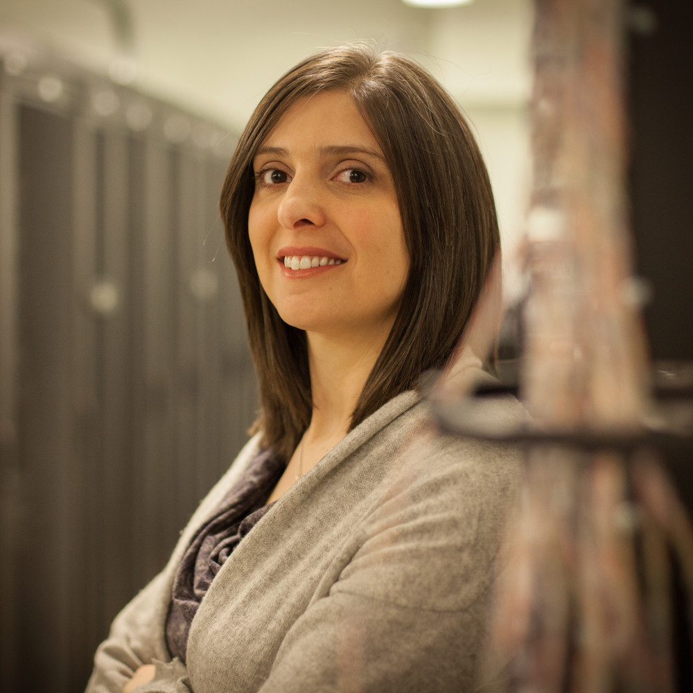Professor Lora Ramunno is pictured from the waist up. She stands with her arms crossed, with her body positioned at a 45 degree angle from the camera. The background is blurred.