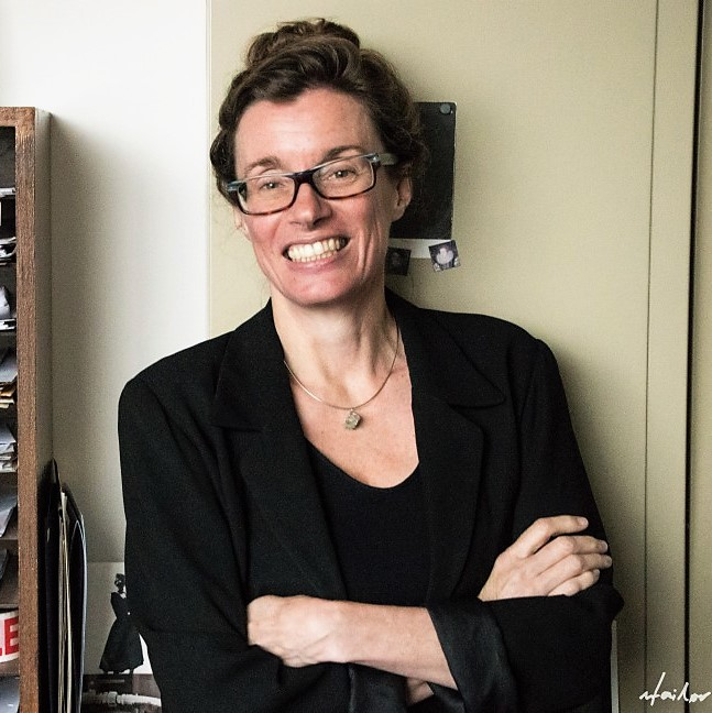 Professor Deryn Fogg is standing in her office wearing a black shirt and a black blazer