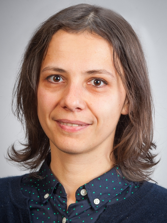 Prof. Laura Dumitrescu in front of a grey background wearing a polka-dot button-up shirt with a dark blue cardigan.
