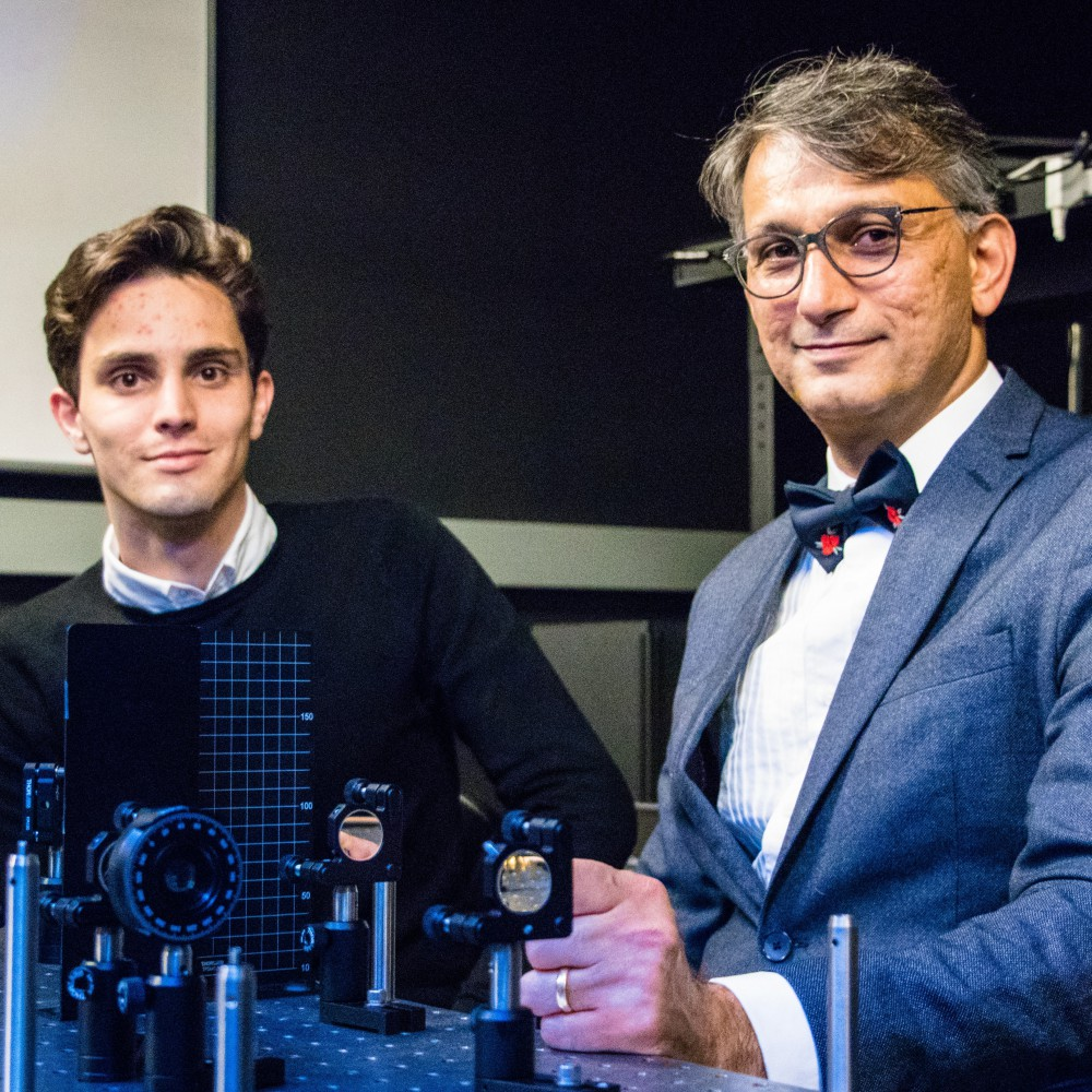 From left to right, graduate student Hugo Larocque sits beside Professor Ebrahim Karimi. In front of them are structures used for optics experiments