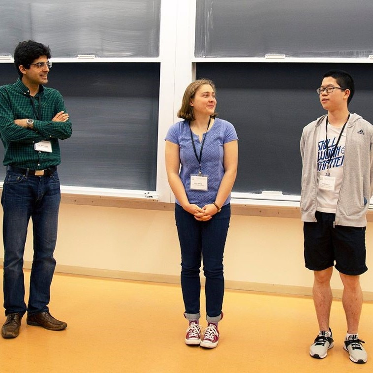 (from left to right) Professor Hadi Salmasian, and undergraduate students Havi Ellers and Xiaomin Li, stand side by side, around 1 metre apart, in front of a blackboard.