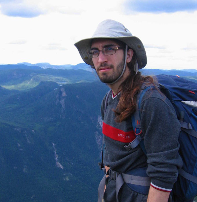 Graduate student Étienne Léveillé-Bourret is standing at the top of a mountain in the Regional Park of Hautes-Gorges of the Malbaie River. Behind him, we see a valley and another mountain.