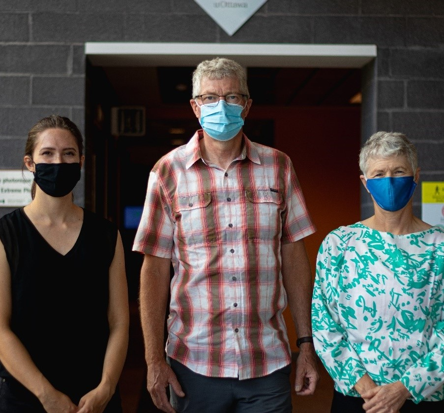 (from left to right) MSc student Evelyn Tennant, Professor Tom Al and Research Associate Erika Revesz stand side-by-side in the lobby of the Advanced Research Complex, all wearing face masks.