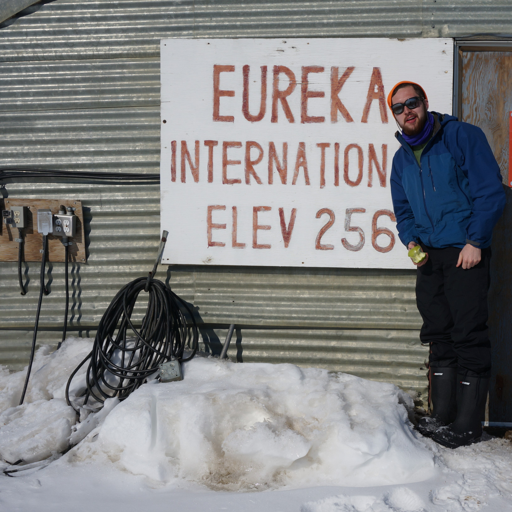 Graduate student Graham Colby is standing outdoors in front of a cabin with his feet in the snow. He is dressed in winter gear and wearing sunglasses. Behind him, affixed on the cabin, is a sign that says EUREKA INTERNATIONAL ELEV 256.