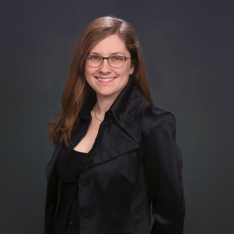 Standing in front of a black background, Gwen Bailey is wearing a black shirt and a black blazer