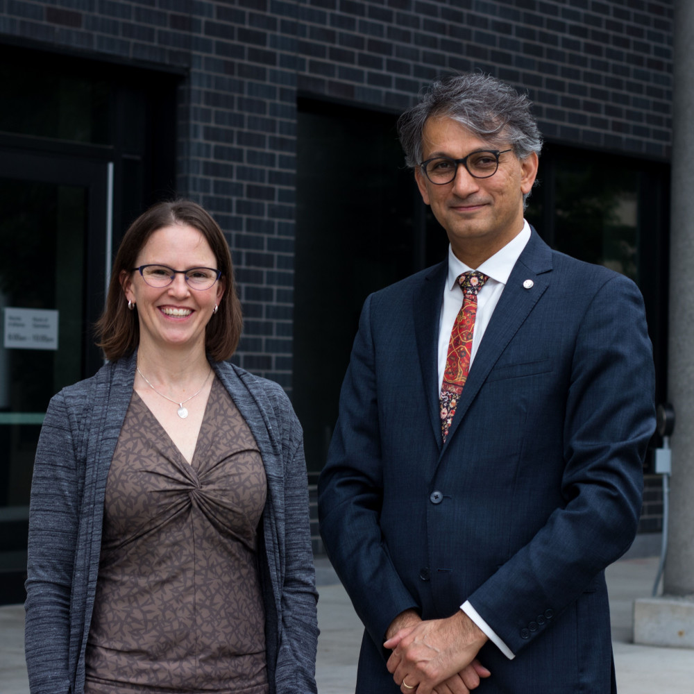 Professors Alison Flynn and Ebrahim Karimi are standing outside, at the entrance of STEM building, between two concrete columns.