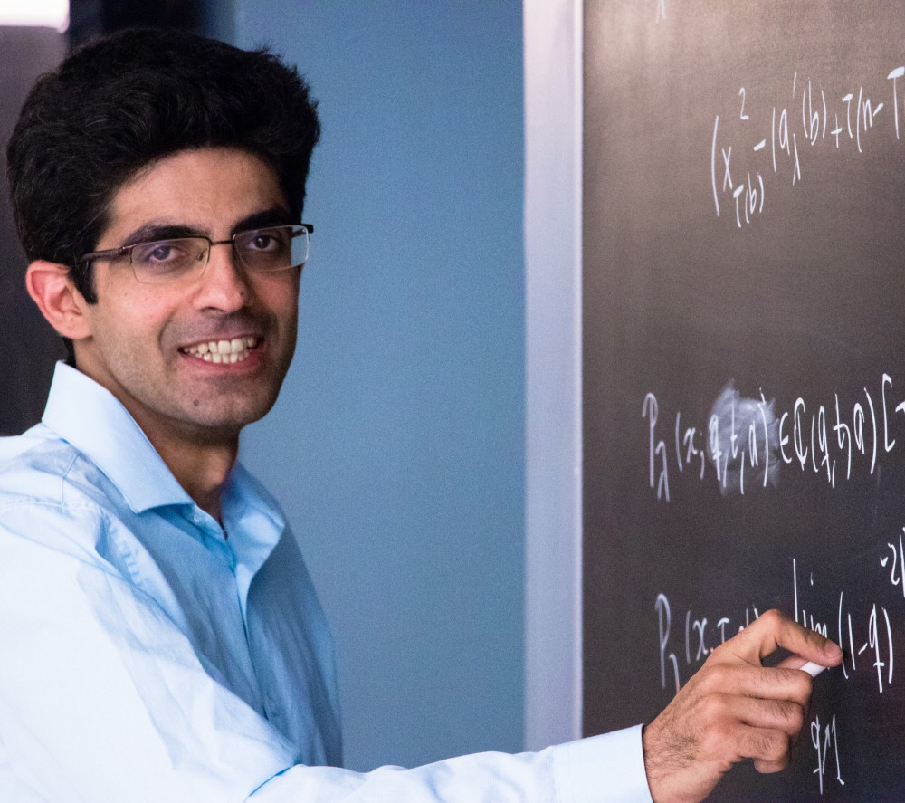Professor Hadi Salmasian in a light blue button up shirt stands in front of a blackboard writing mathematical formulas upon it with white chalk
