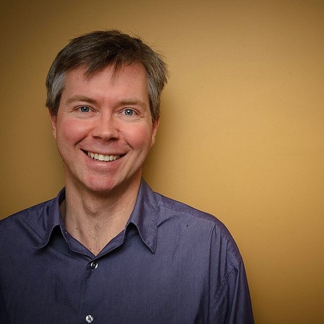 Professor Jeremy Kerr in a blue button-up shirt is standing on front of a yellow background. He is in the left of the frame