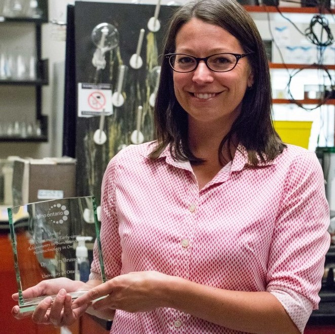 Professor Jaclyn Brusso in a light pink button up shirt is standing in her lab holding her Nano Ontario Award for Outstanding Early-career Achievements