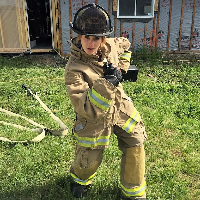 Dressed head-to-toe in firefighting gear, PhD student Jennifer Keir stands in front of a house under construction. Laying on the ground behind her is a heavy-duty firefighting hose