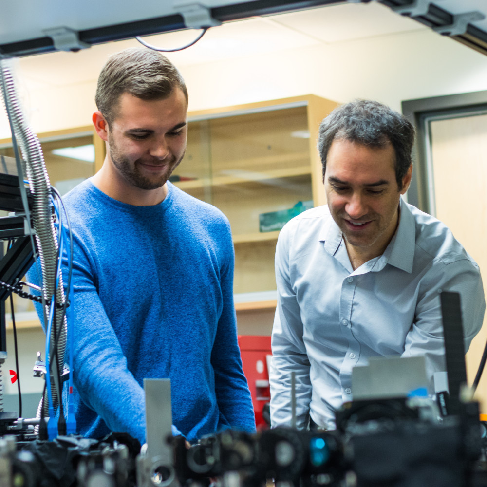 Jean-Michel Ménard and his PhD student Nicolas Couture are standing behind a table looking down at terahertz spectroscopy research equipment.