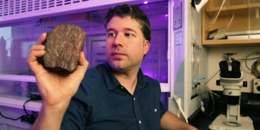 Johnathan O'Neil, professor at the University of Ottawa's Department of Earth and Environmental Sciences, holds a sample of rock taken from the area where he and the research team discovered microfossils of the oldest life forms ever found on Earth
