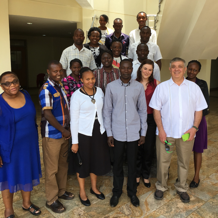 Professor Scaiano is standing at the bottom of a staircase along with Research Associate Anabel Lanterna and 15 members of his team of African researchers.