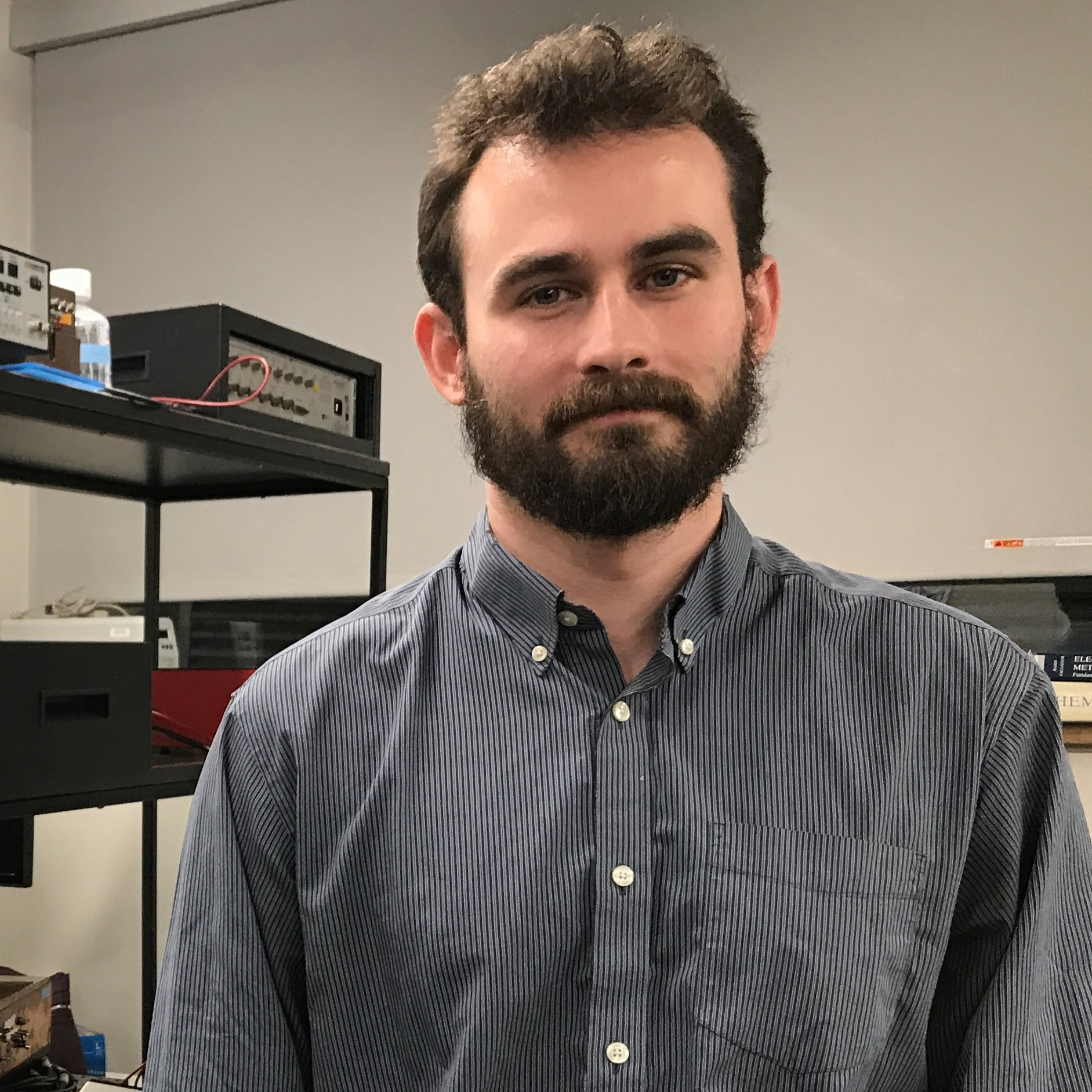 PhD student Kyle Briggs standing in front of a black shelving unit upon which laboratory material can be found