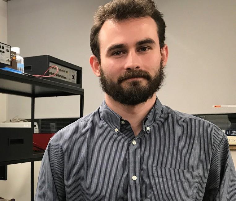 Kyle Briggs, étudiant au doctorat, debout devant une étagère noire sur laquelle du matériel de laboratoire est déposé