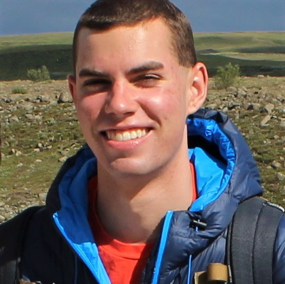 Headshot of undergraduate coop student Lucas Philipp, wearing blue, hooded jacket and a backpack, and standing in front of a background of tundra