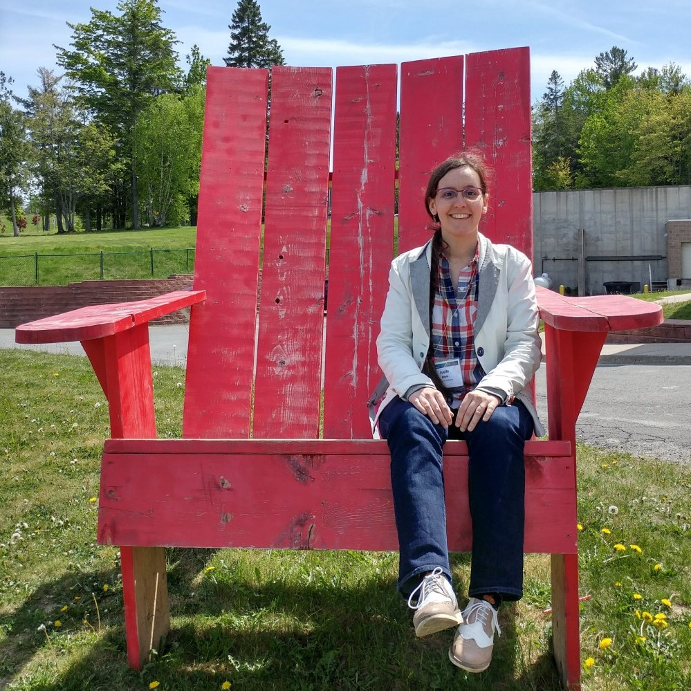 Lucile Devin siting on a giant red Adirondack garden chair.