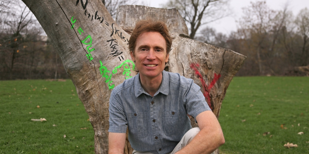 Frithjof Lutscher, professeur au Département de mathématiques et de statistique à l'Université d'Ottawa, devant un arbre mort couvert d'équations