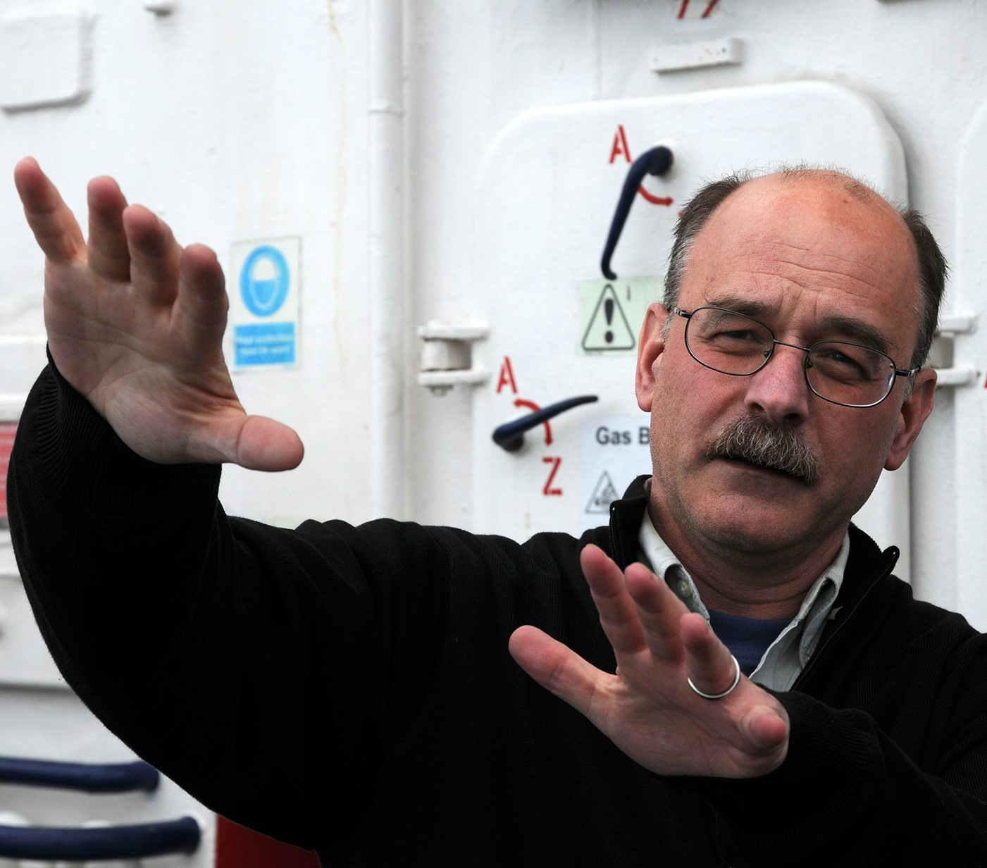 Professor Hannington is standing on the deck of a research vessel. He is wearing a black sweater, and his arms are raised and pointing towards the camera as he is explaining something.
