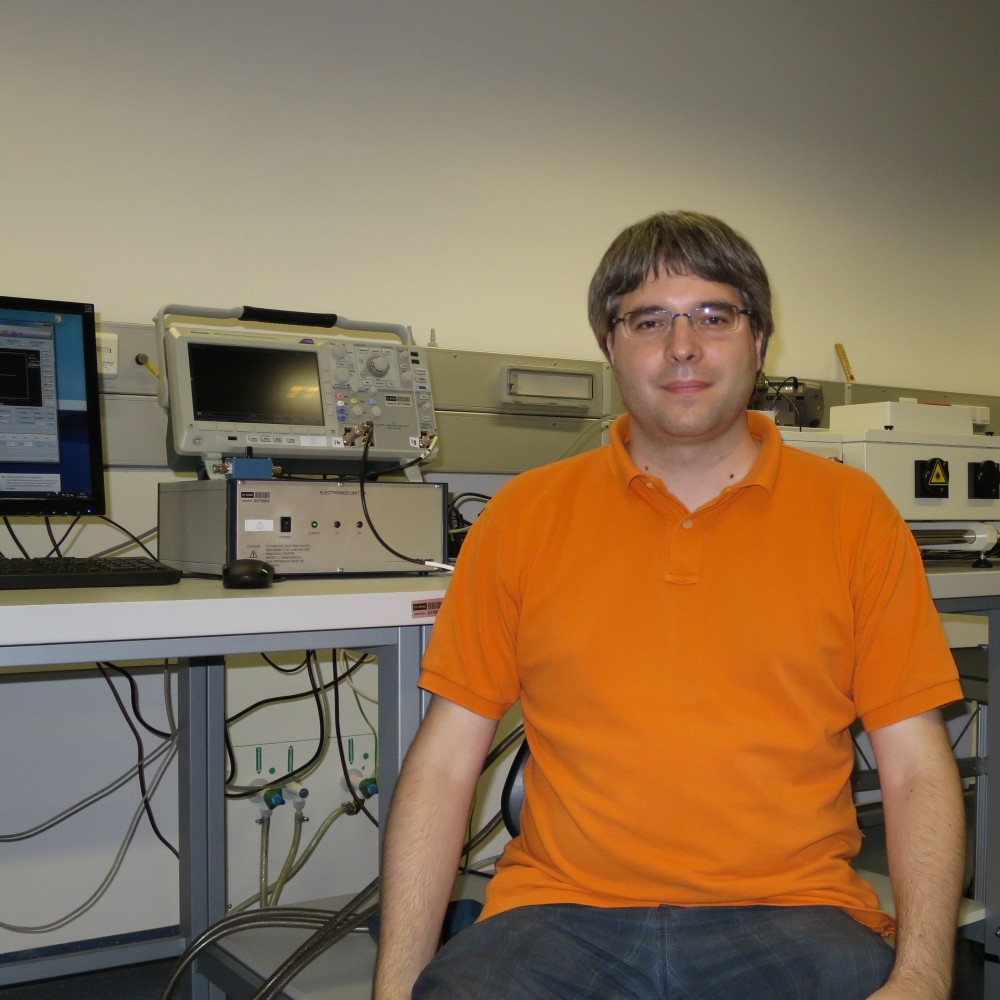 Chemistry postdoctoral fellow Markus Greisser sitting in laboratory in front of a row of computers and electronic machines wearing a bright orange shirt