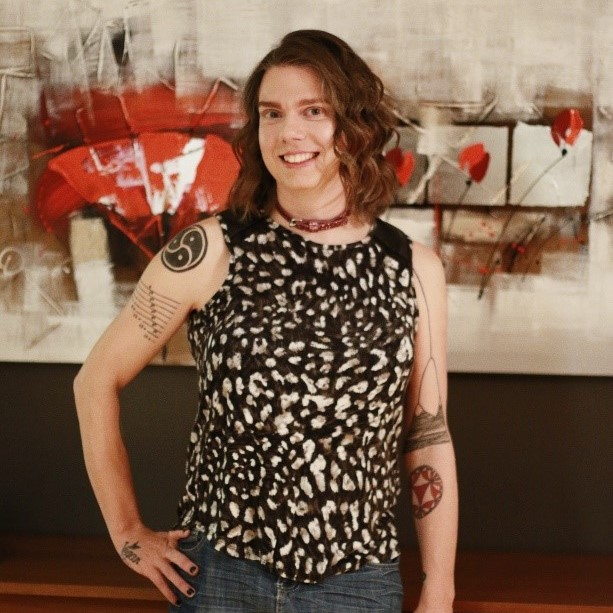 Professor Stacey R. Smith? stands in front of an abstract painting, with one hand on her hip.