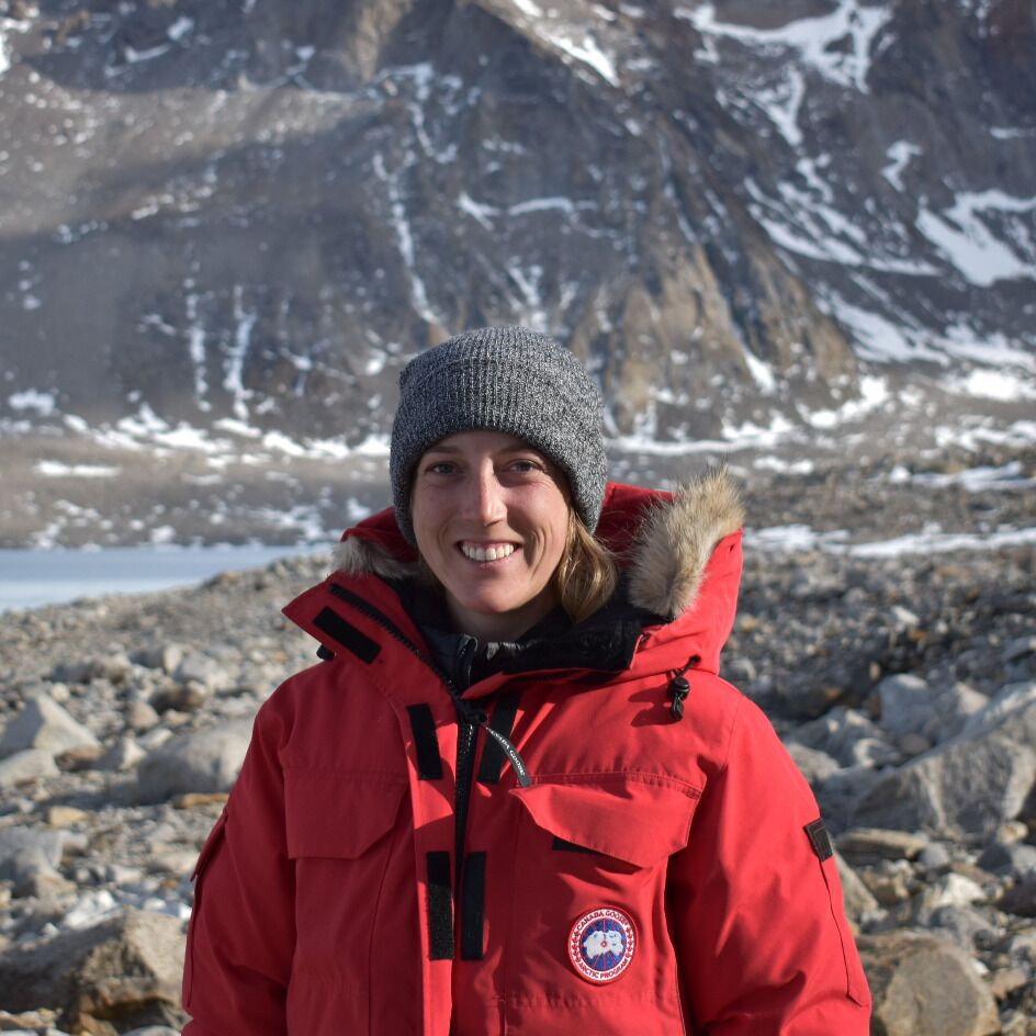 Graduate student Nicole Marsh is standing outdoors, wearing a red parka and a grey tuque. Behind her we see a landscape of rocks and a partially snow-covered mountain.