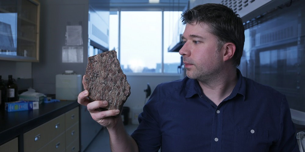 Jonathan O'neil holding what could be one of the oldest rock