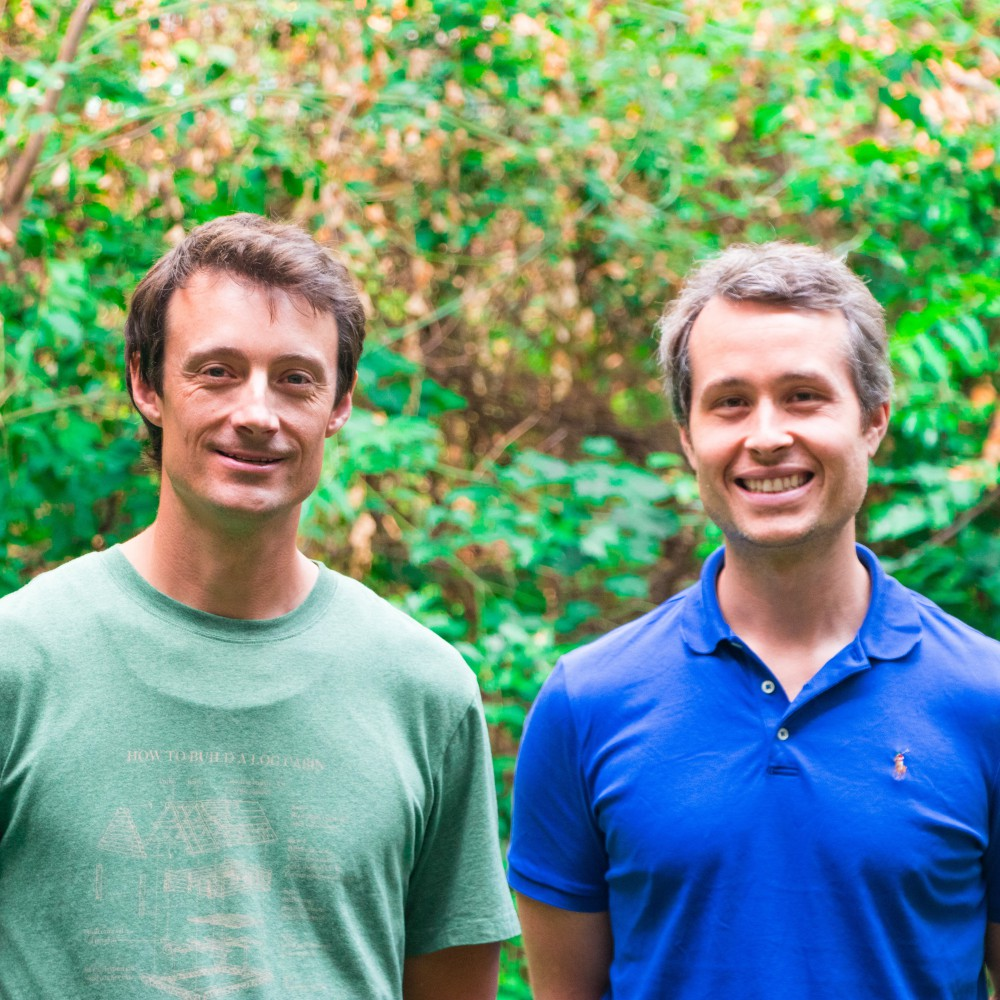 From left to right, postdoctoral fellow Daniel Munro, wearing a green t-shirt, and Professor Matthew Pamenter, wearing a blue polo shirt. They are looking into the camera and standing in front of trees and greenery