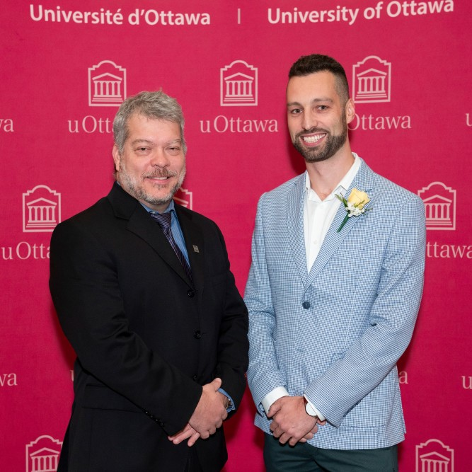 (from left to right) Dean of the Faculty of Science Louis Barriault and alumnus Patrick Nadeau,  standing in front of a red background harbouring multiple uOttawa logos.