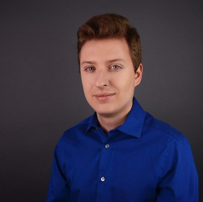 Patrick Szell, PhD student in Chemistry, in front of a dark grey background wearing a deep blue button- up shirt.
