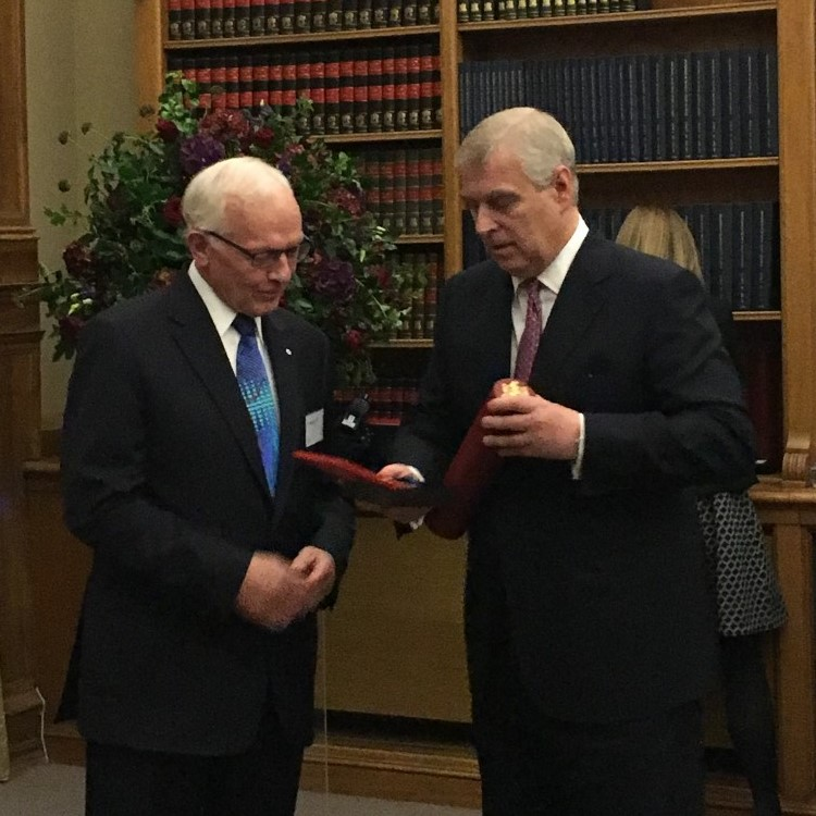 Standing in front of a large wooden bookshelf and a bouquet, Prof. Paul Corkum, on the left, accepts the Royal Medal of the Royal Society of London from Prince Andrew, on the right. Both men are sporting black suits, Prof. Corkum with a blue tie and Princ