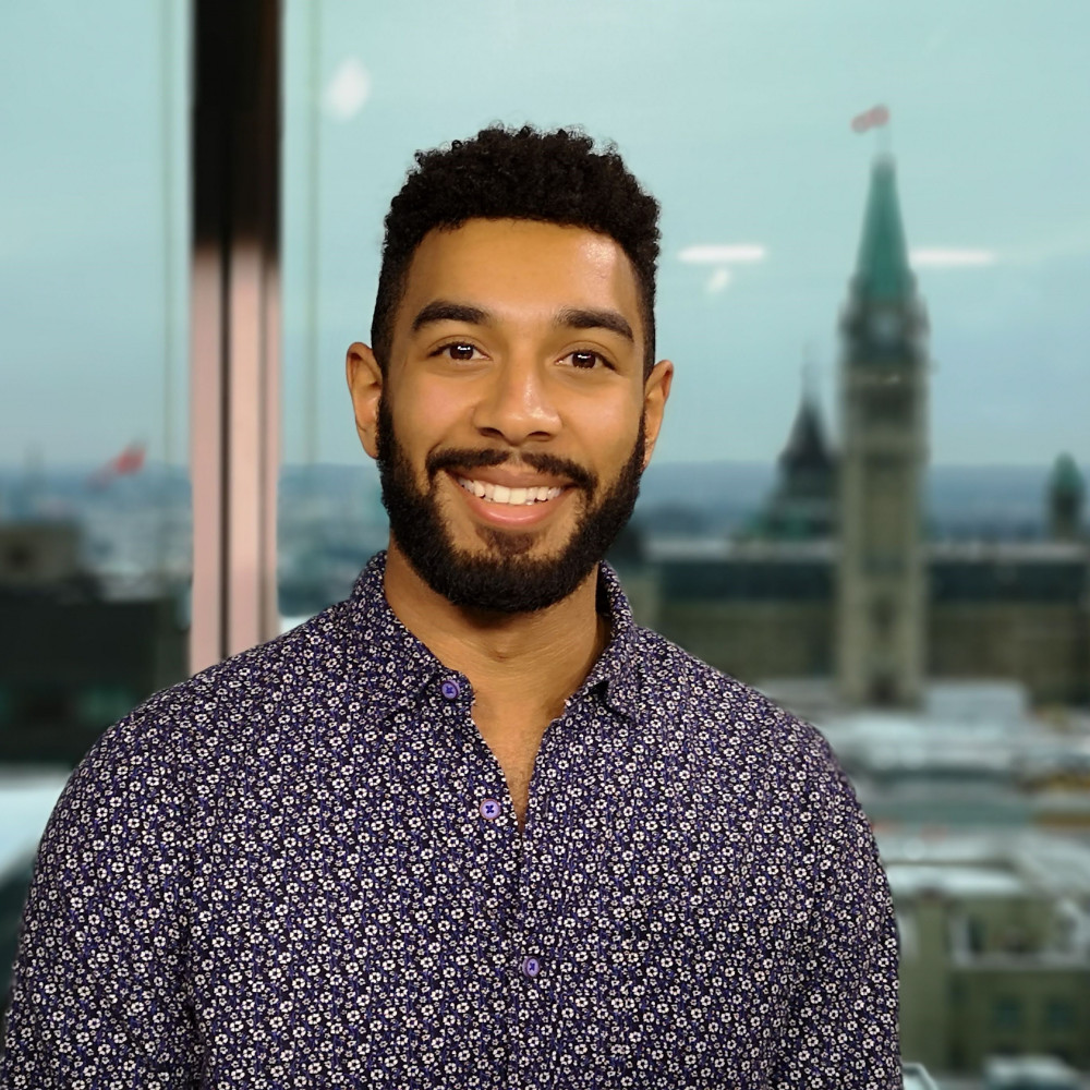 Headshot of PhD student Peter Soroye, wearing a blue and white patterned shirt. We see a window behind him, and the Canadian parliament is seen through the window