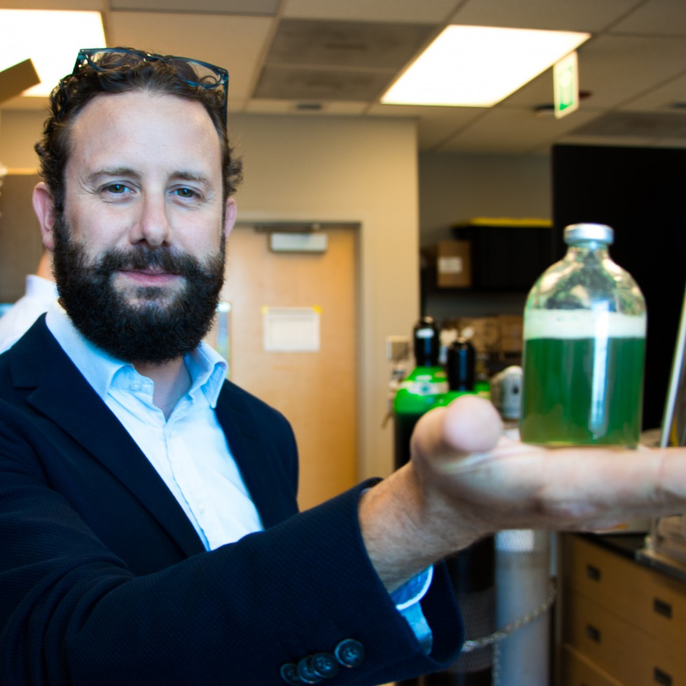 Professor Alexandre Poulain is standing in his lab. He is showing the camera a small bottle full of green liquid known as purple non-sulphur bacteria