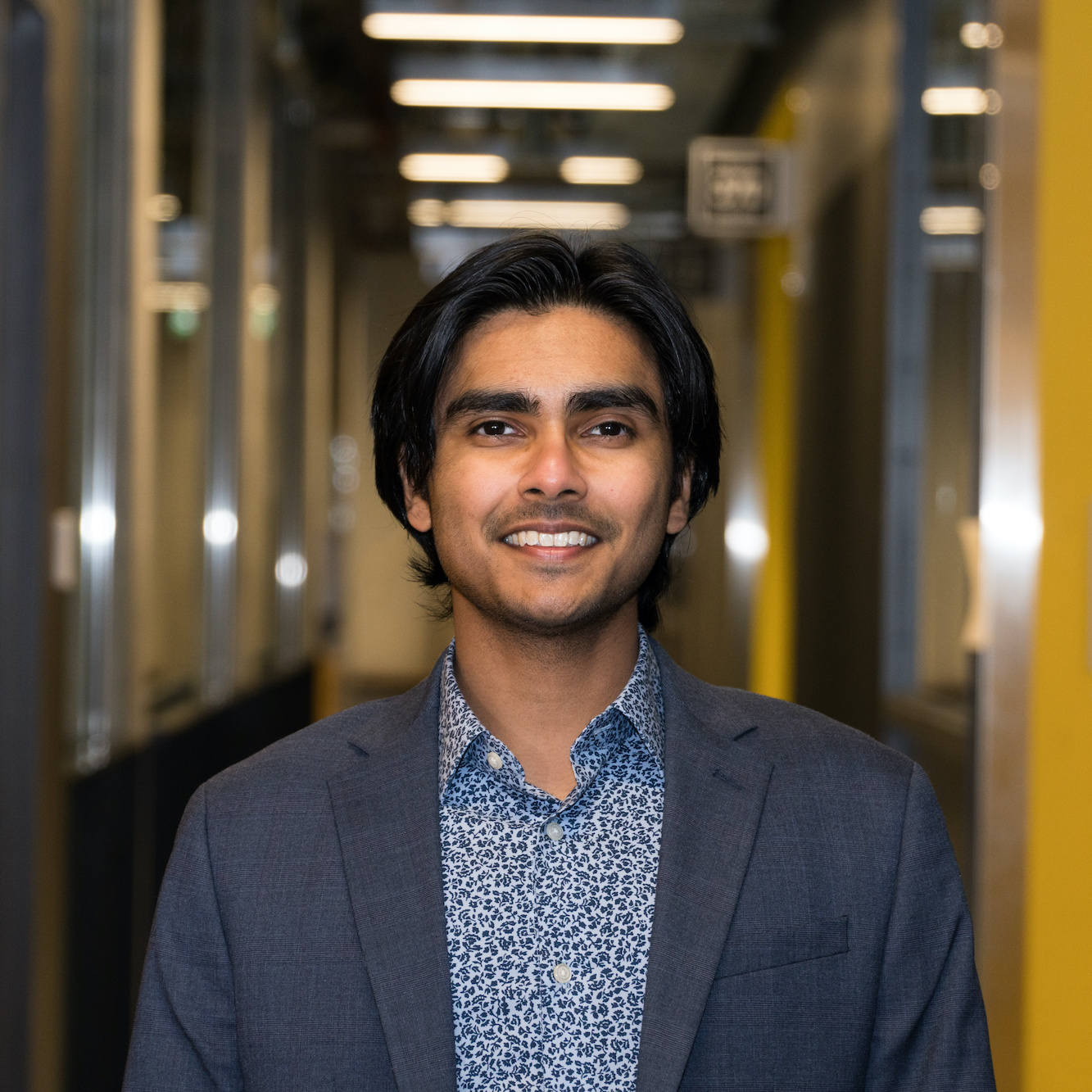 Master's student Rabib Islam is seen from the chest up, wearing a light blue patterned shirt and a grey blazer. We see a corridor of the uOttawa Stem Complex behind him