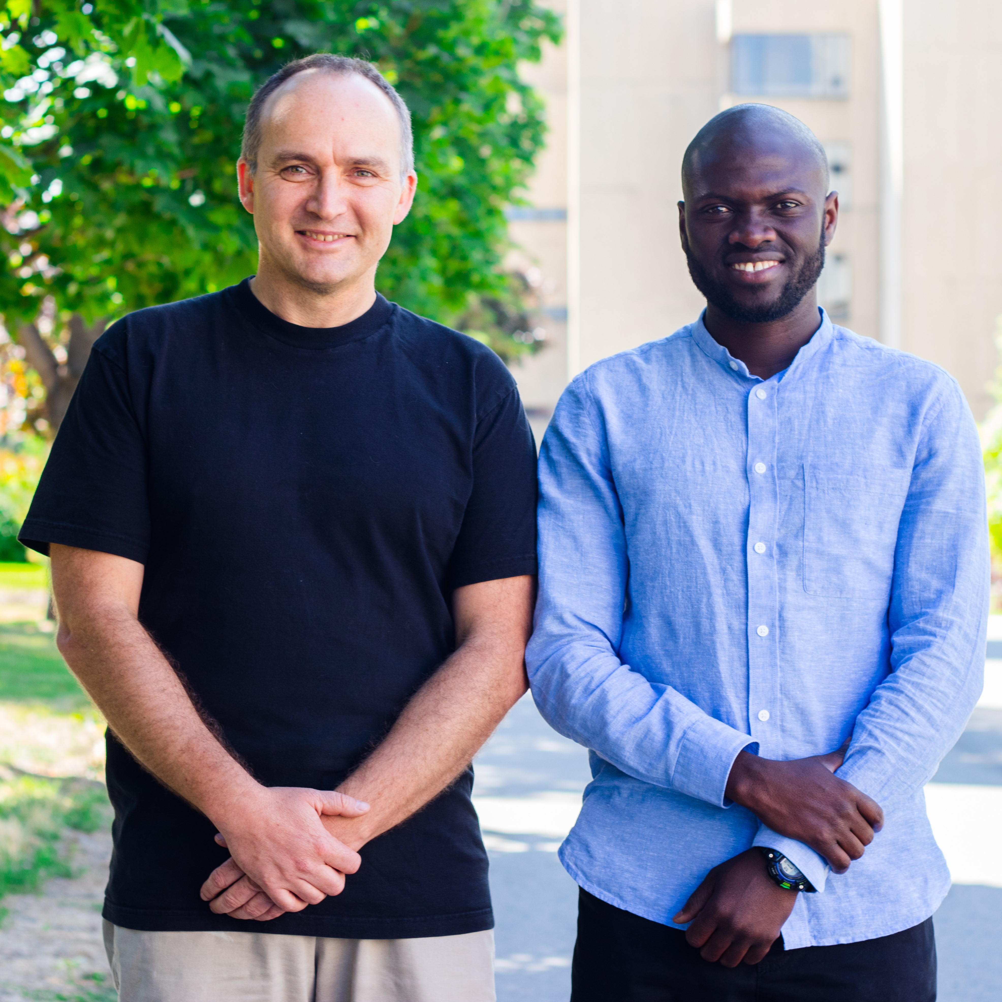 Professor Rafal Kulik (left) and his PhD student Yousouph Cissokho (right) are standing outdoors, on uOttawa campus. There are trees behind them.