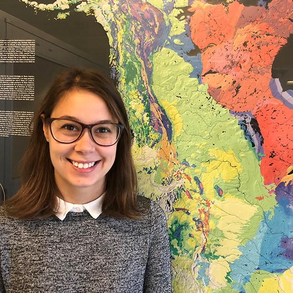 Photo of PhD student Renelle Dubosq, who is standing in front of a poster showing a multicolored map of North America