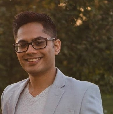 PhD graduate Ron Shah is seen from the chest up, wearing a light grey blazer over a light grey sweater. We see a blurred background of leaves behind him.